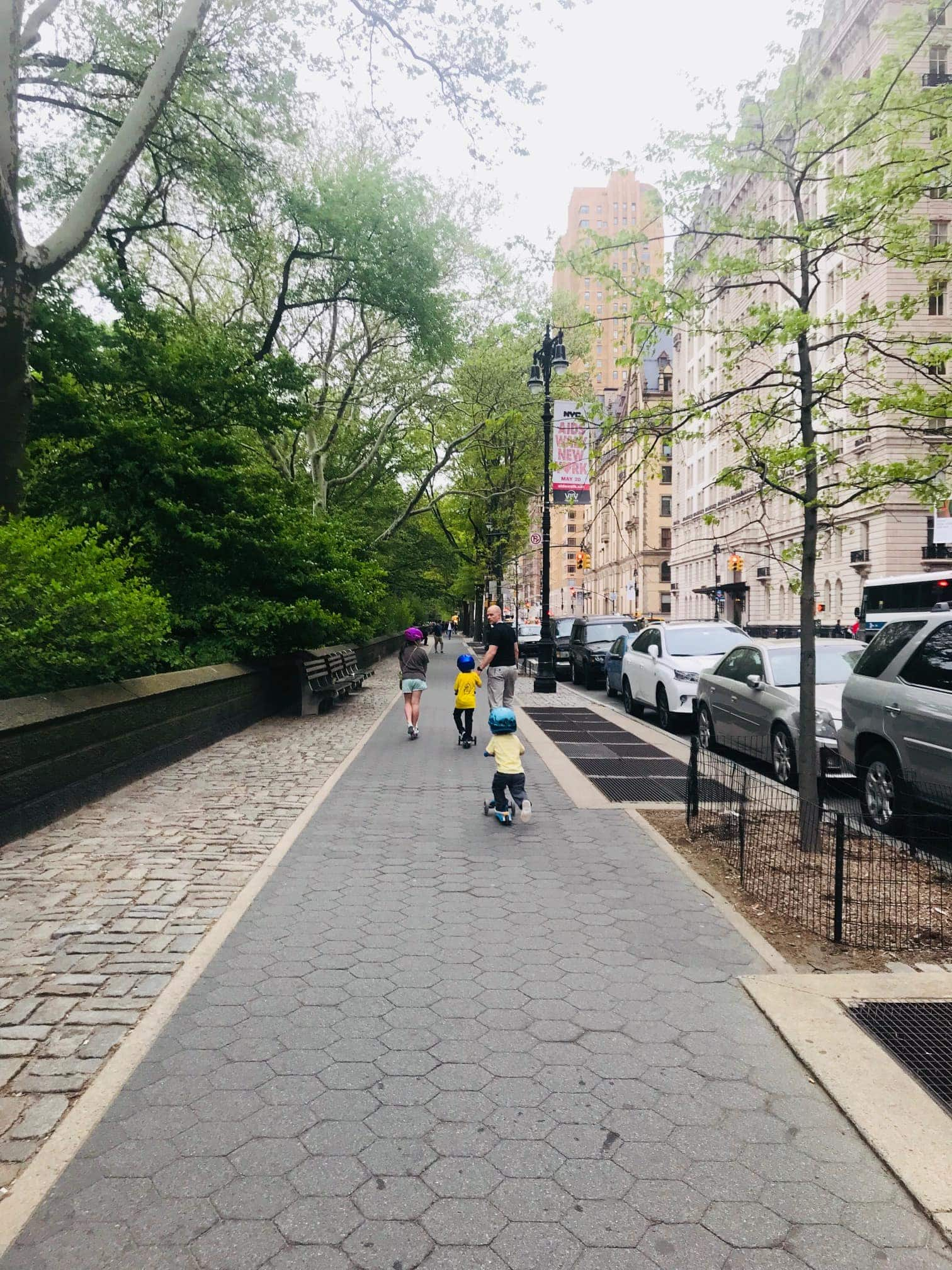 Kids scootering down a sidewalk in the city