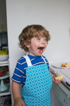 Eddie in an apron holding a slice of an apple