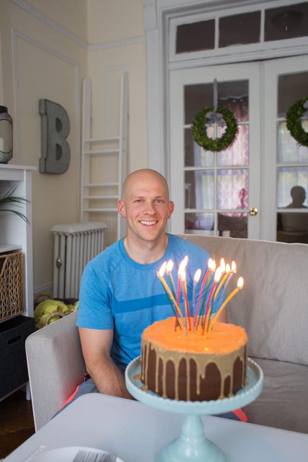 Gordon smiling behind his lit birthday cake