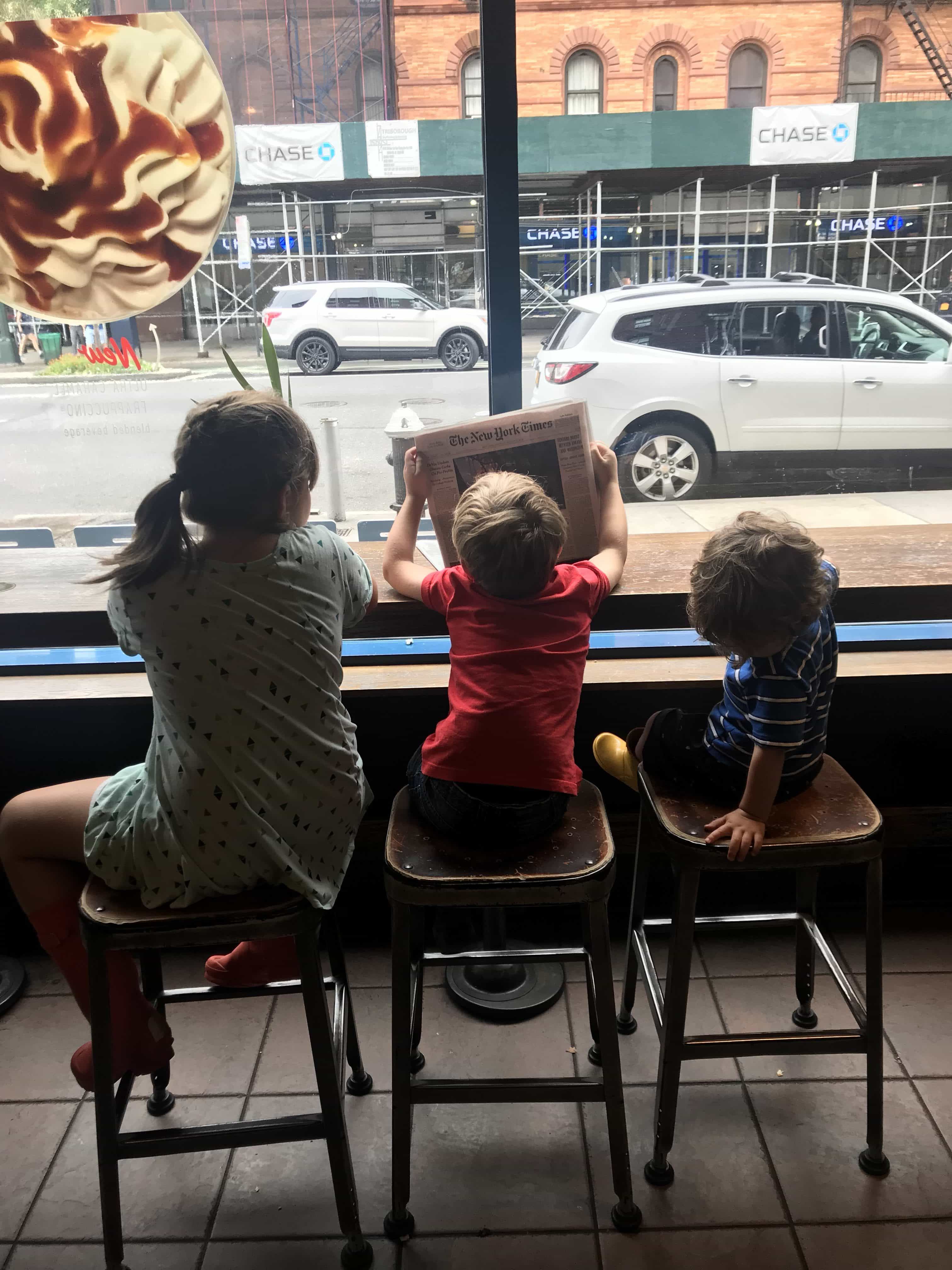 Kids sitting at a bar in front of a window