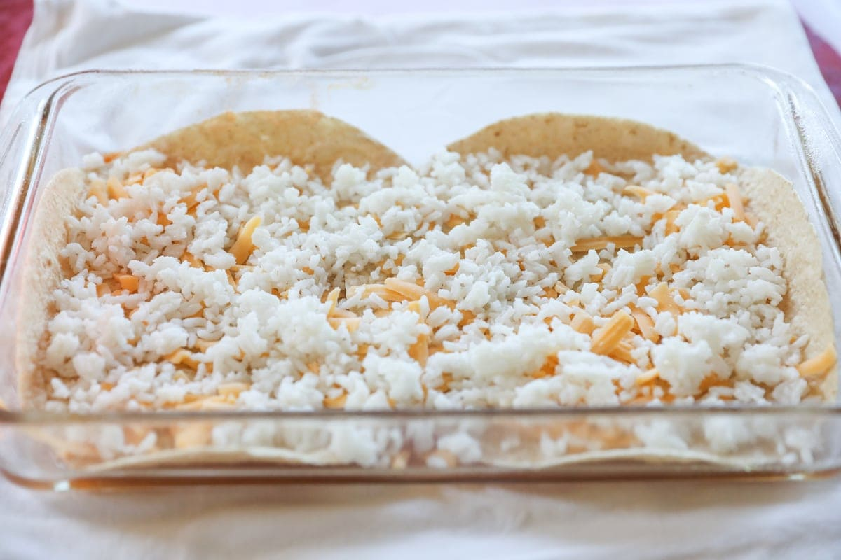 tortillas, rice and cheese layered in baking pan