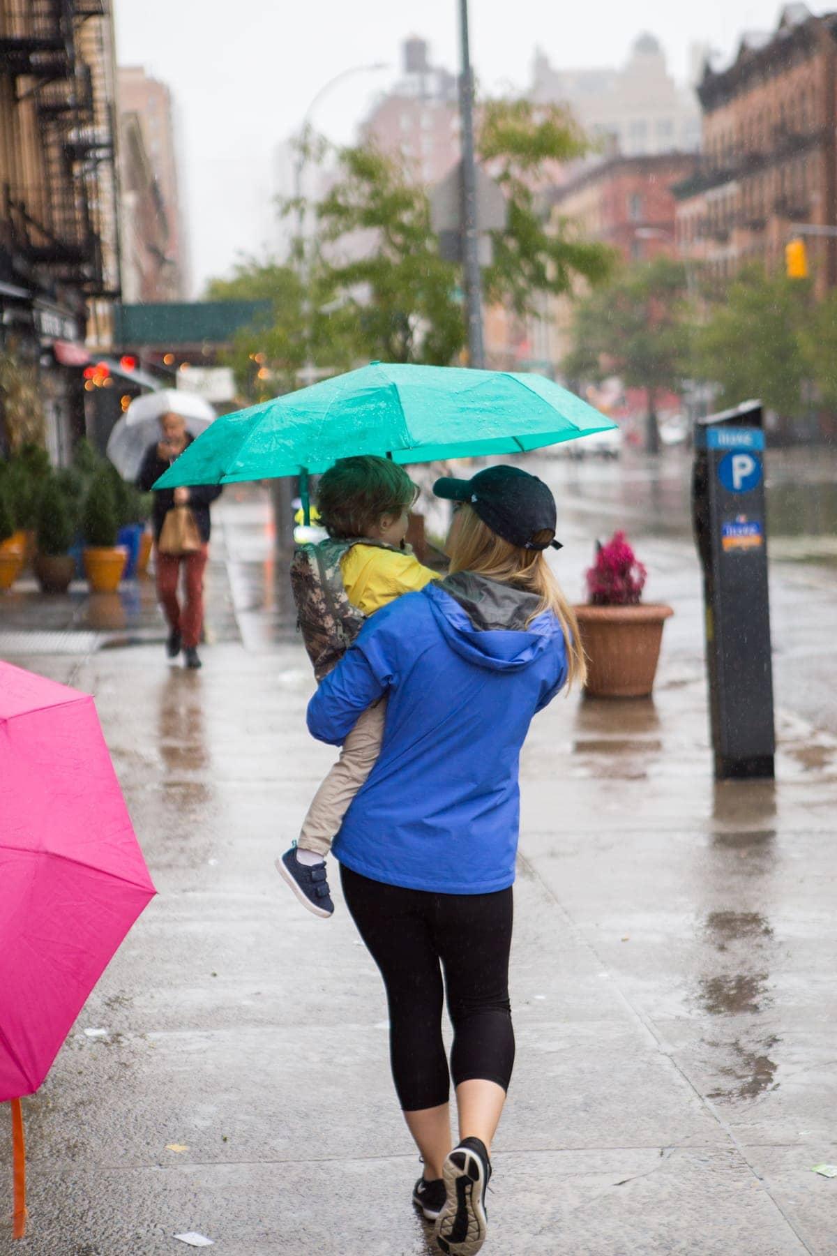 A woman walking down a street holding an umbrella
