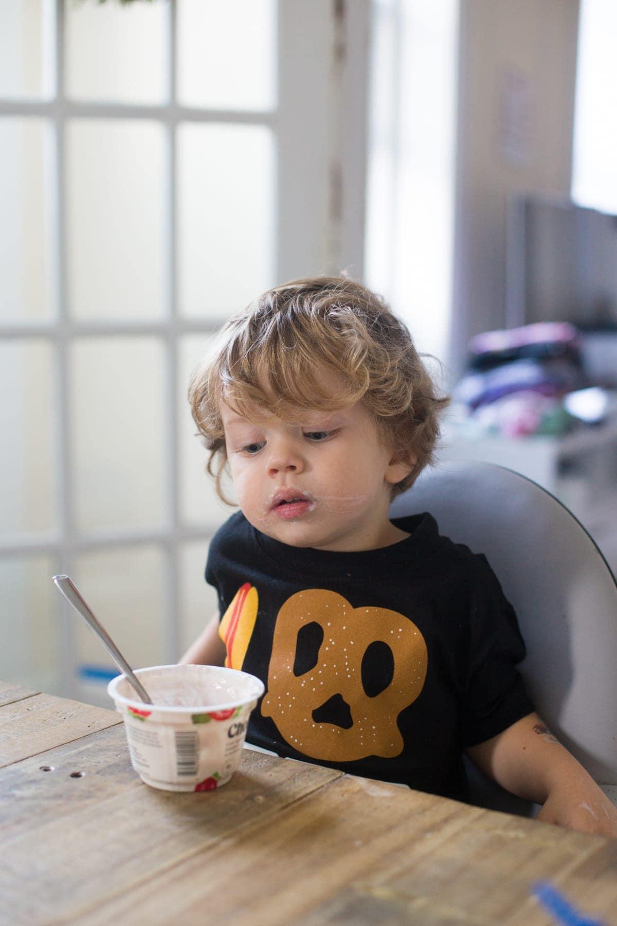 Eddie looking at his yogurt