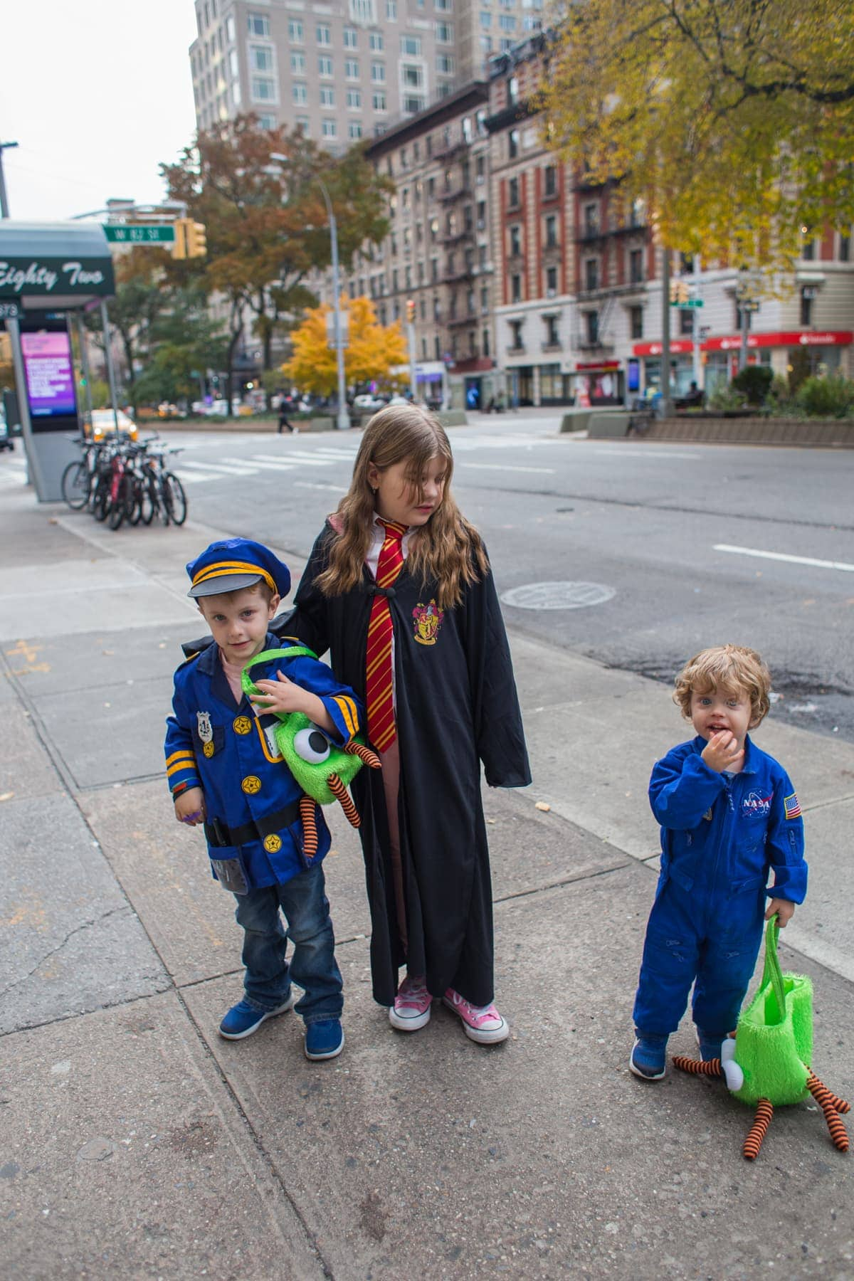 The kids dressed for Halloween on the sidewalk
