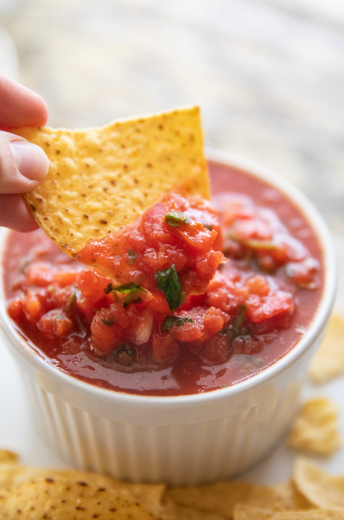 dipping tortilla chip into salsa