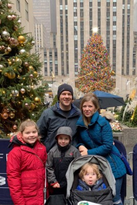 Brennan family in front of Christmas trees outside