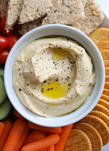 Hummus in a bowl with dipping options around it