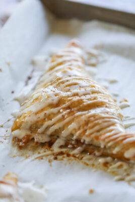 apple turnover with glaze on baking sheet