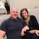 A man and a woman sitting on a couch posing for the camera