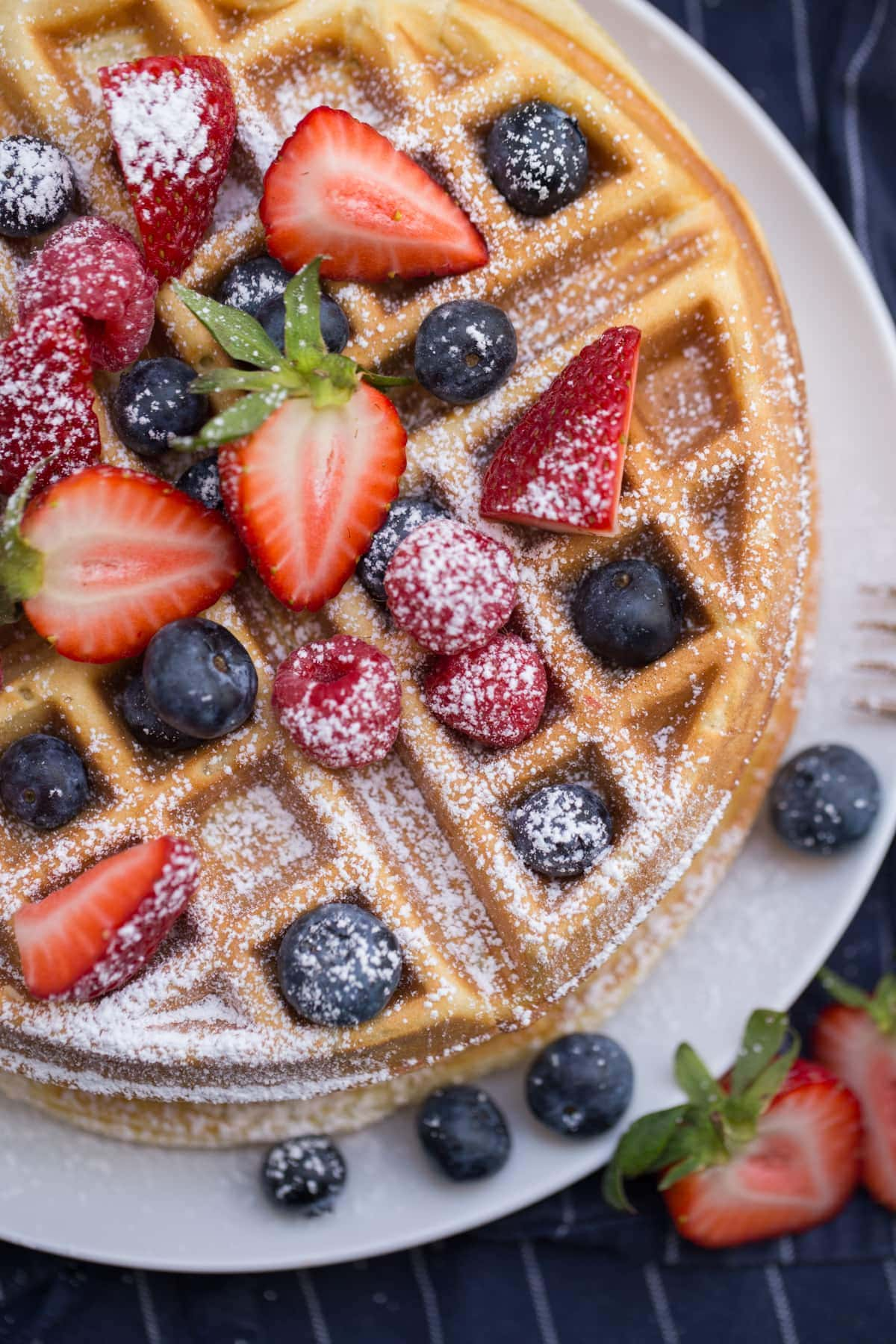 Belgian waffles with berries and powdered sugar