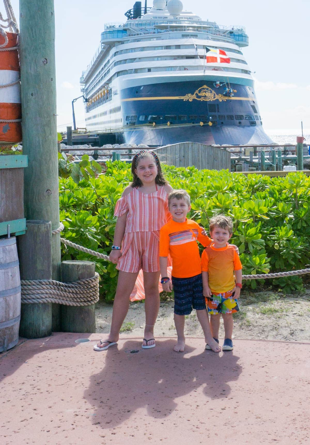 The kids with the Disney cruise ship behind them