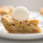 A slice of apple pie with vanilla ice cream on top