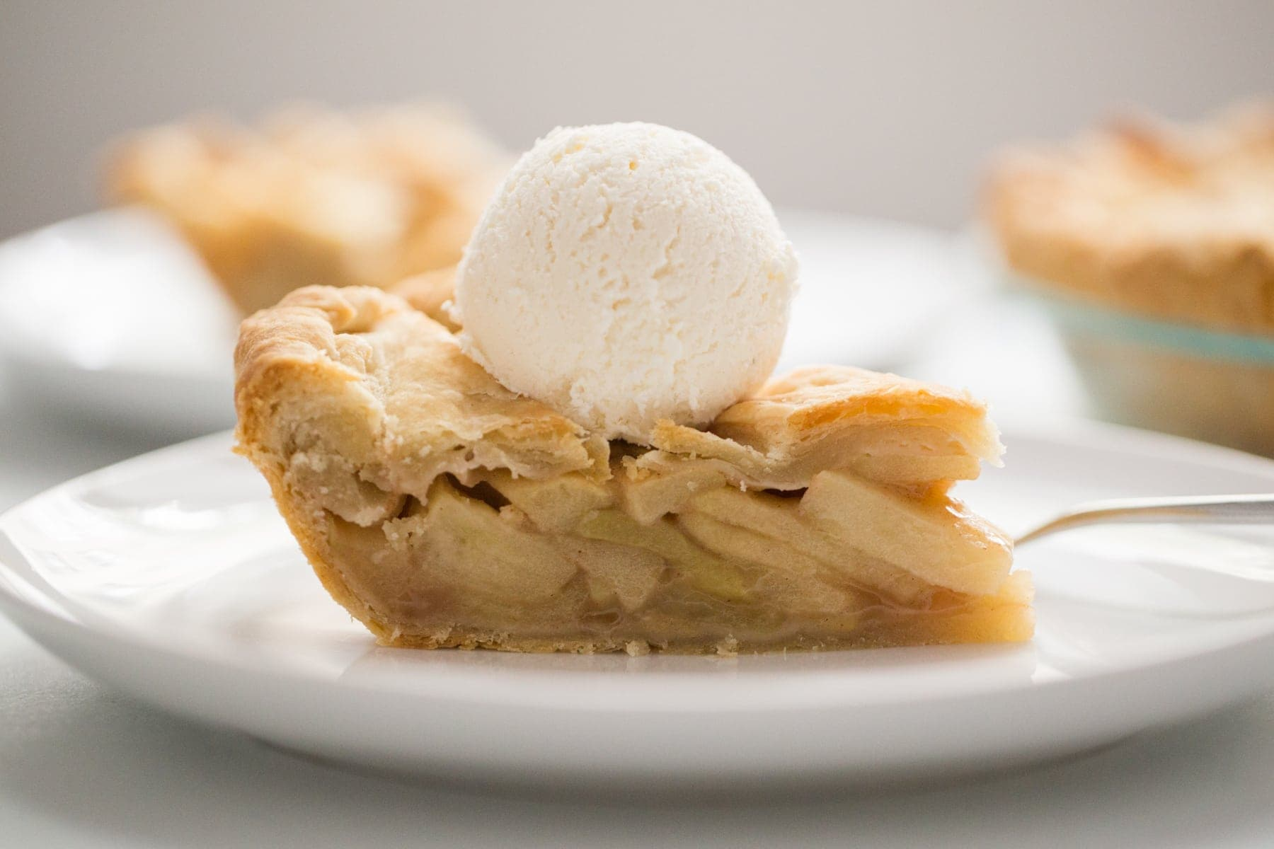 A slice of apple pie with vanilla ice cream on top