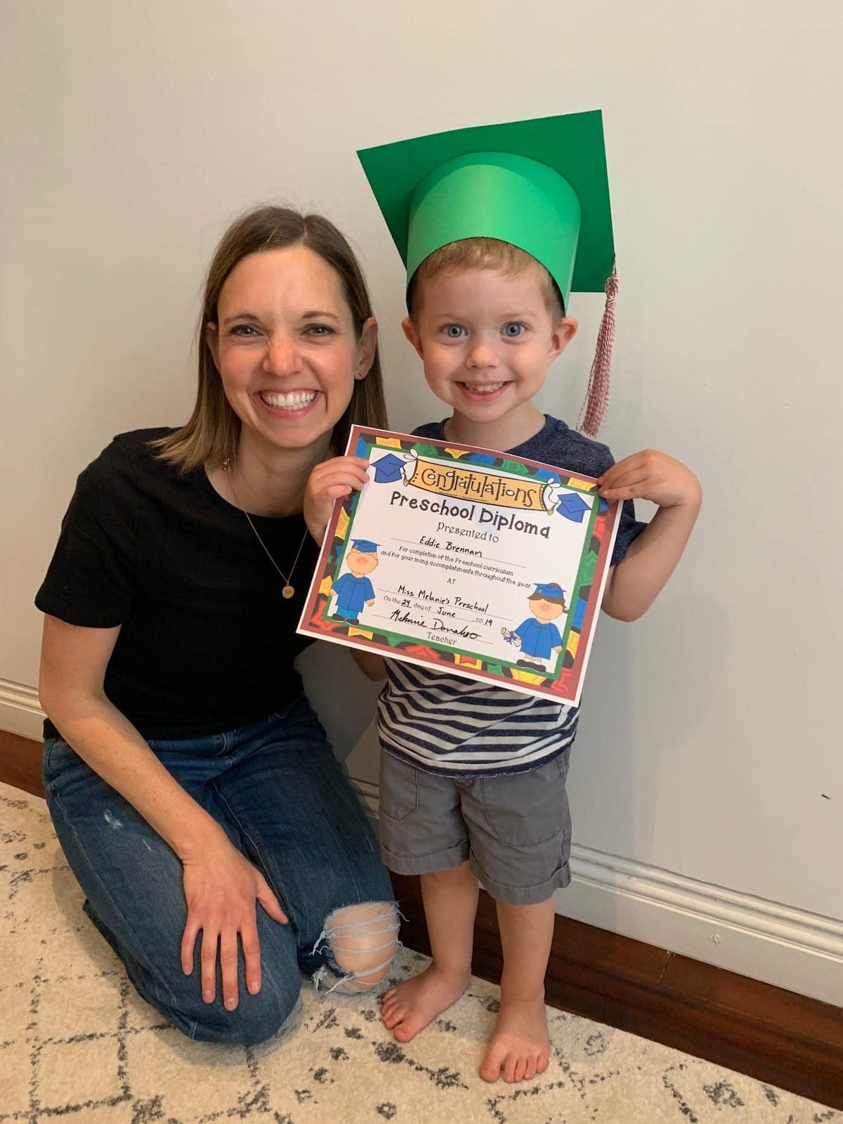 Eddie with his teacher holding a preschool diploma