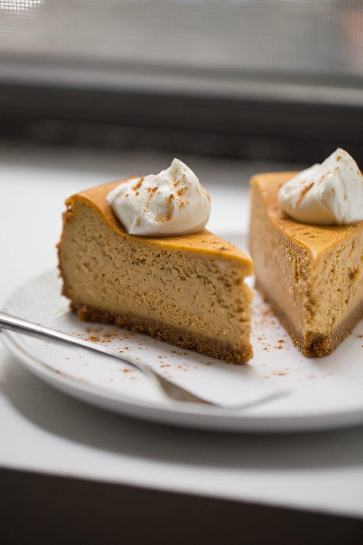 slices of pumpkin cheesecake on white plate