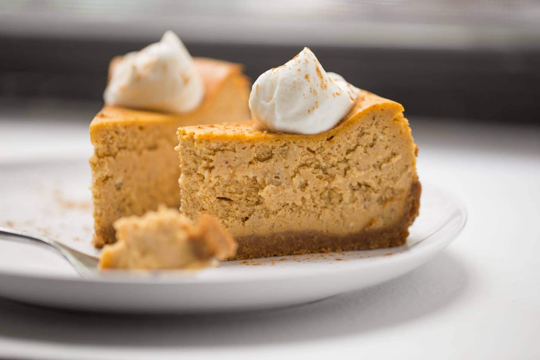 two slices of pumpkin cheesecake with whipped cream