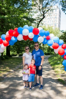Brennan family under fourth of july balloon arch