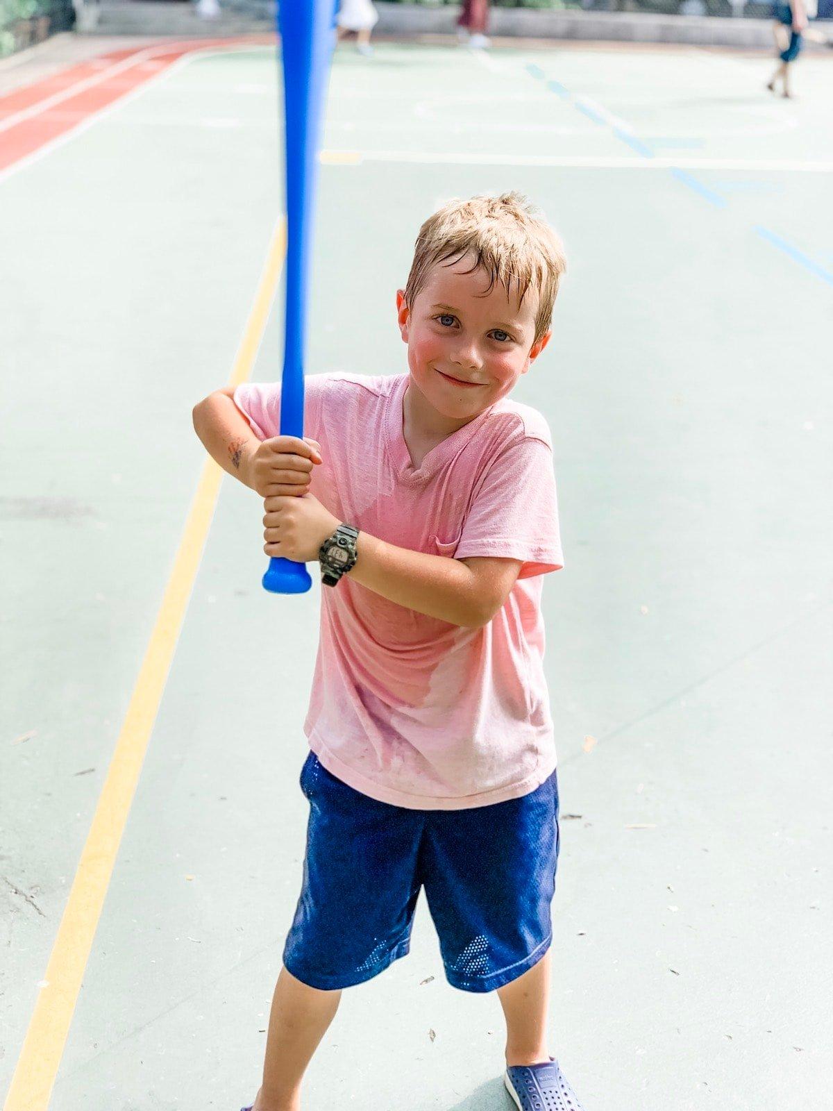 A little boy that is holding a bat