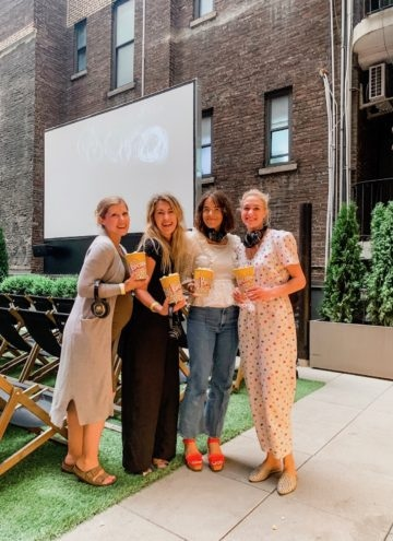 Lauren and friends holding popcorn in front of a projector screen and seats
