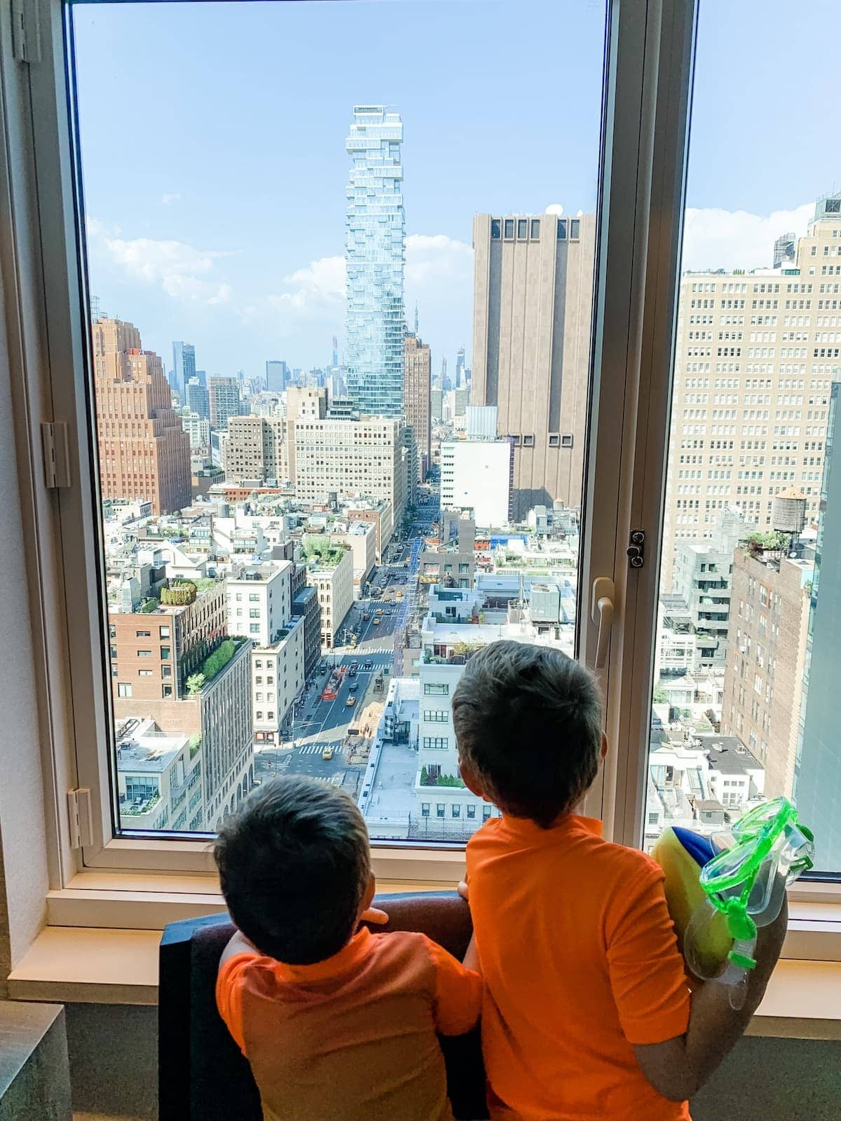 The boys looking outside a window to the city
