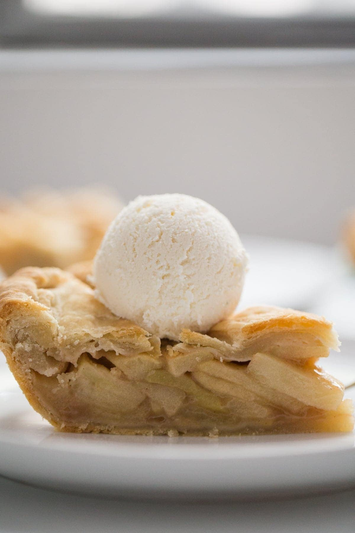 A slice of apple pie topped with vanilla ice cream