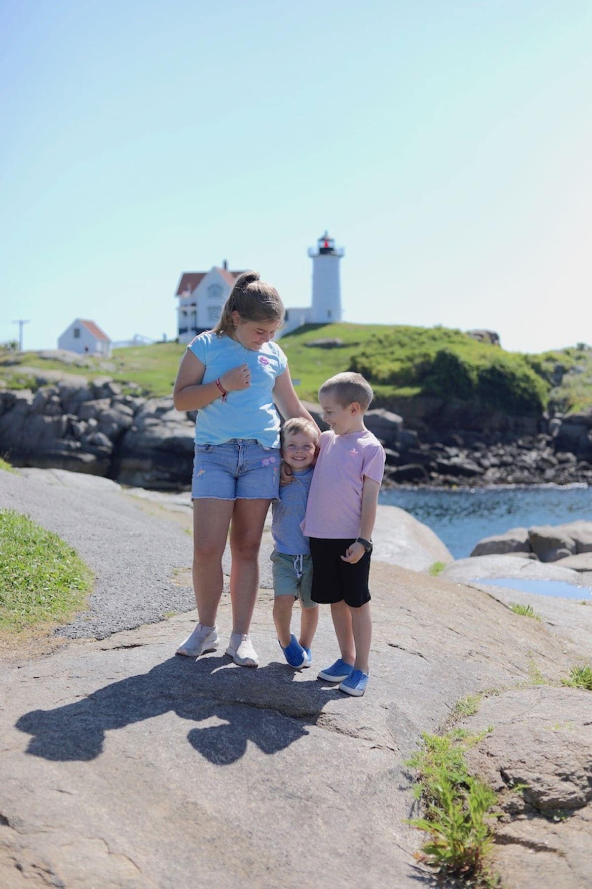 The kids standing on a rock with a light house in the background