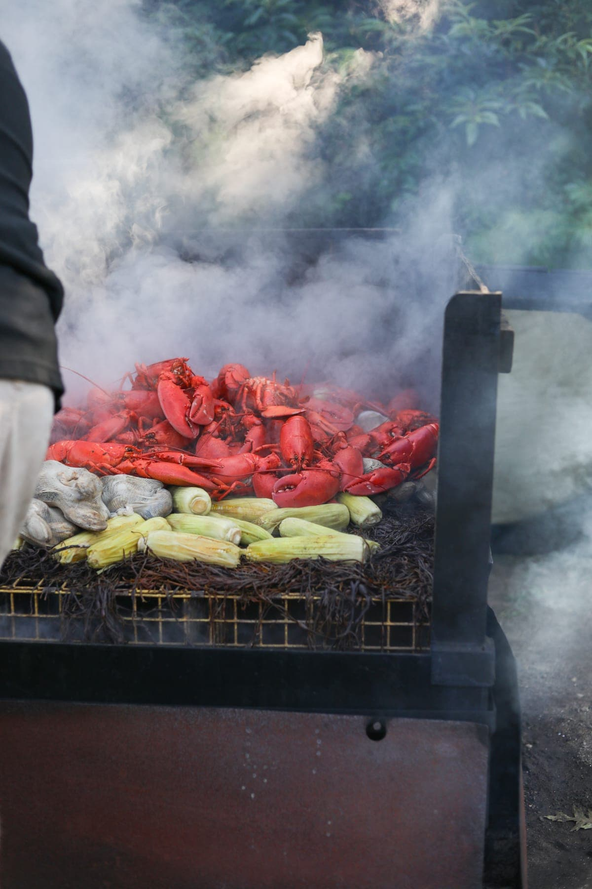 A person cooking lobsters and corn