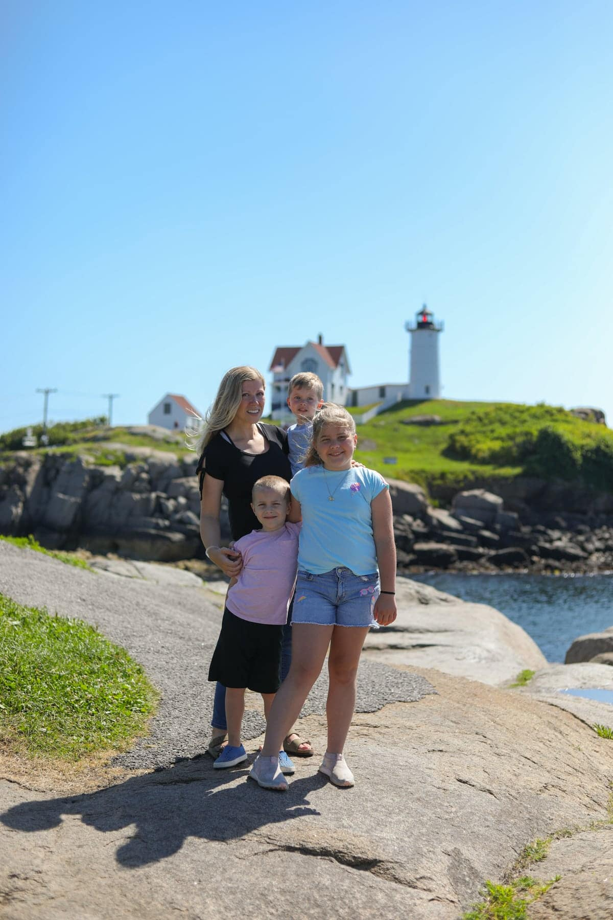 Lauren and the kids at the beach with a lighthouse in the background