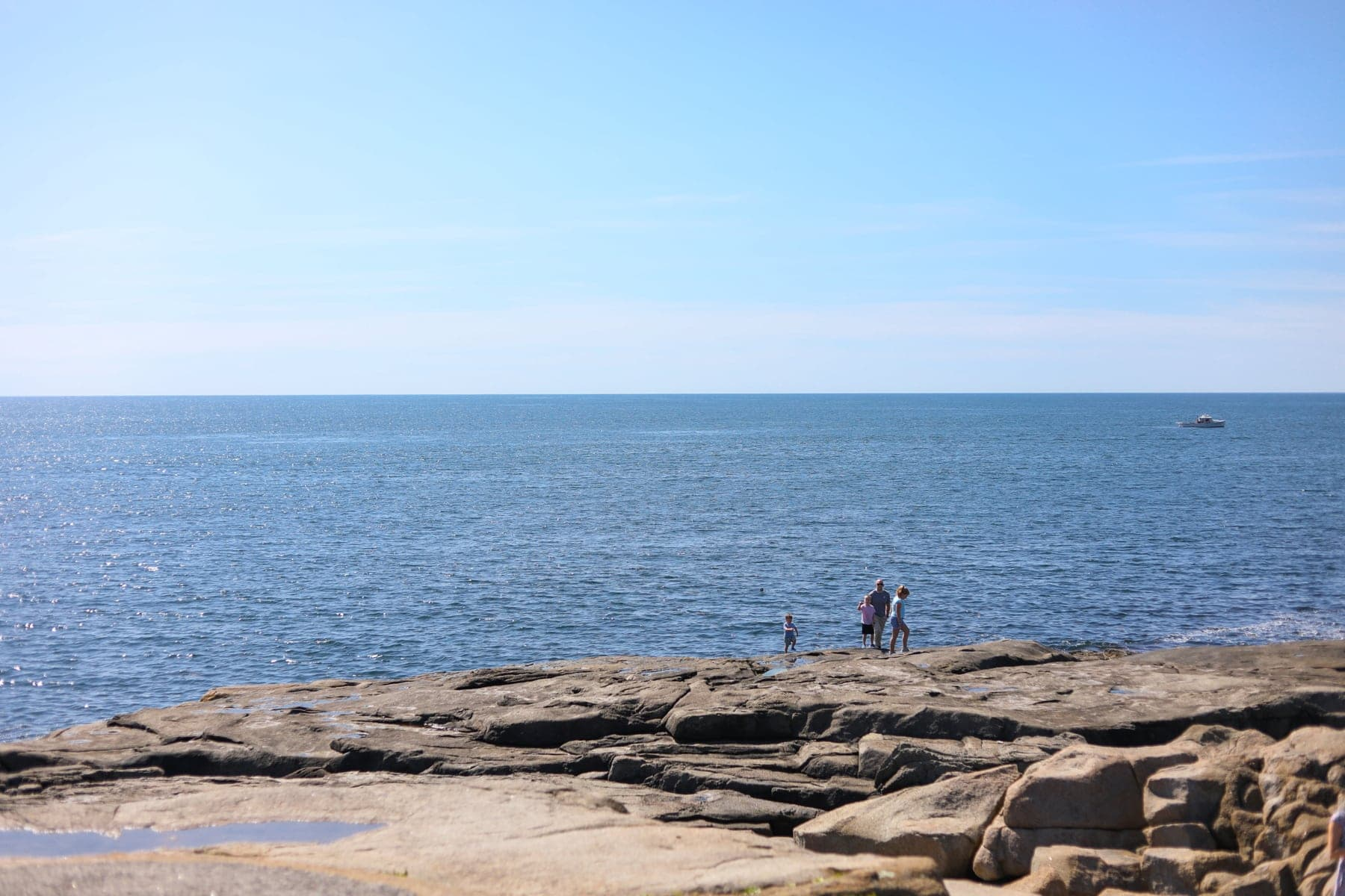 A group of people on a rocky beach next to the ocean