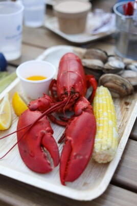 Lobster with butter, lemon and corn on a plate
