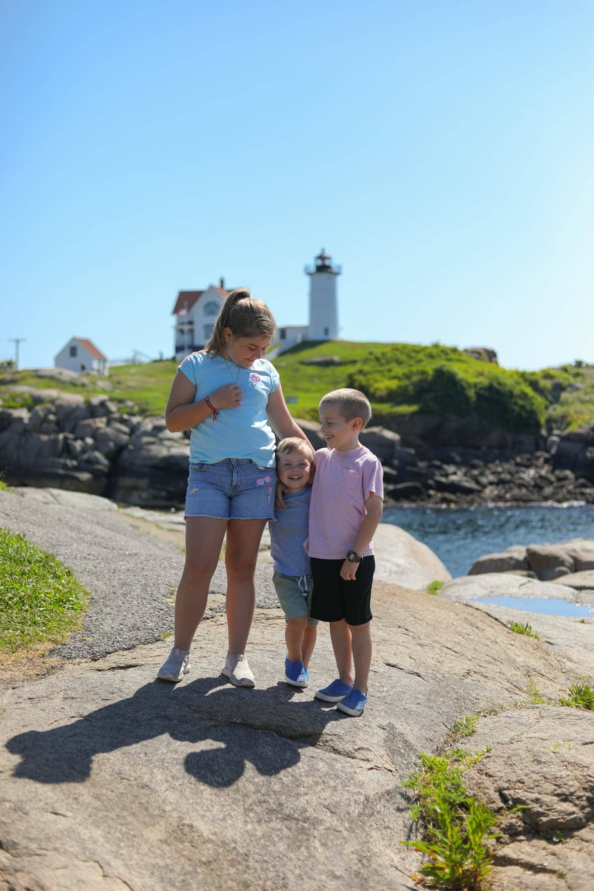 The kids at the beach with a lighthouse in the background