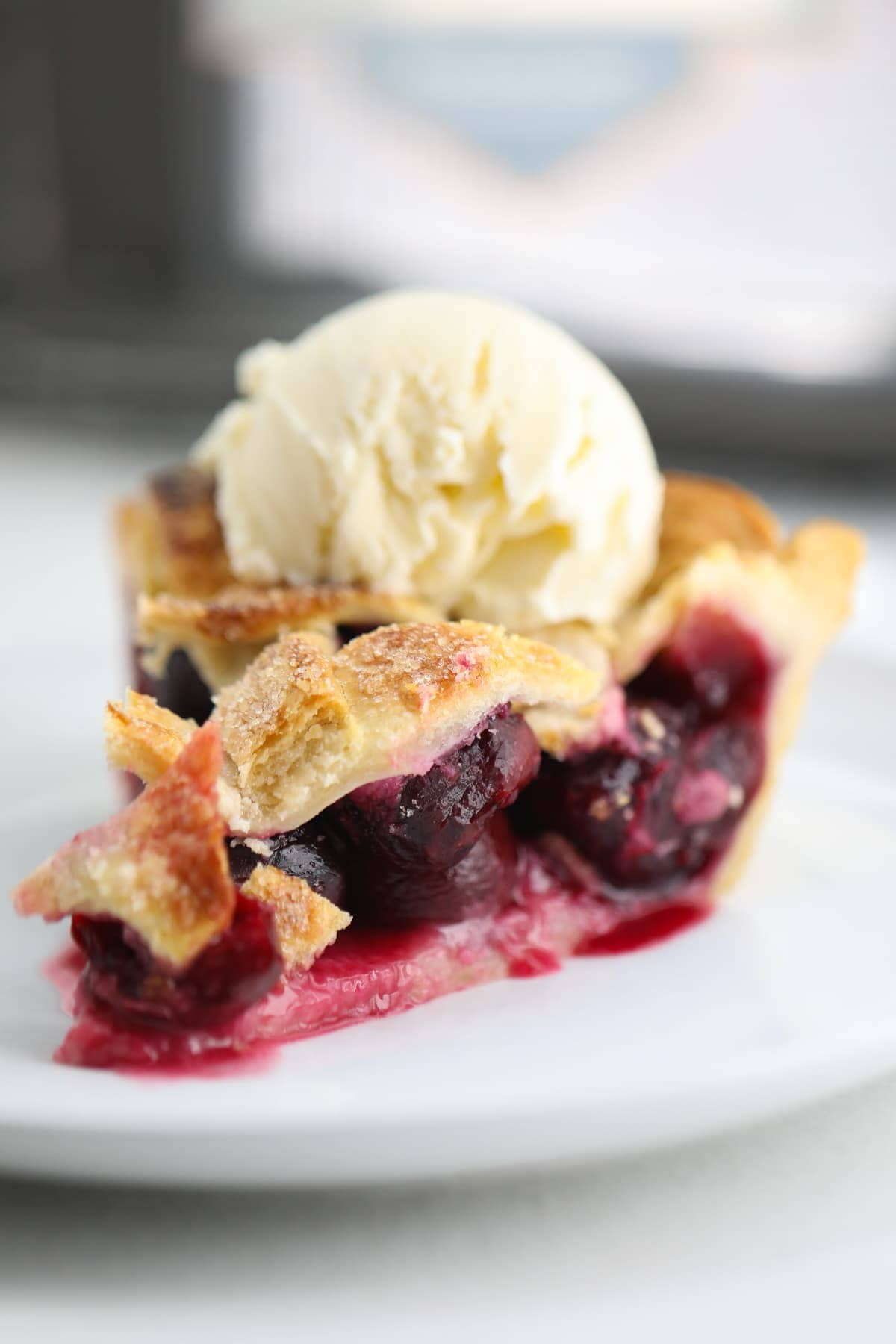 cherry pie on a plate topped with vanilla ice cream