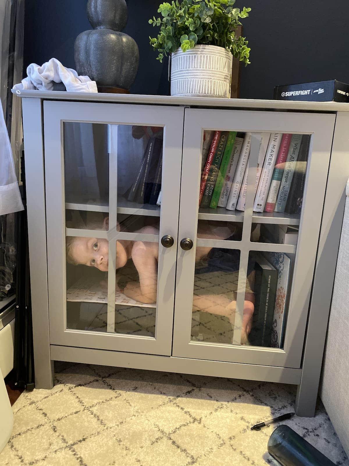 Eddie hiding in a bookshelf