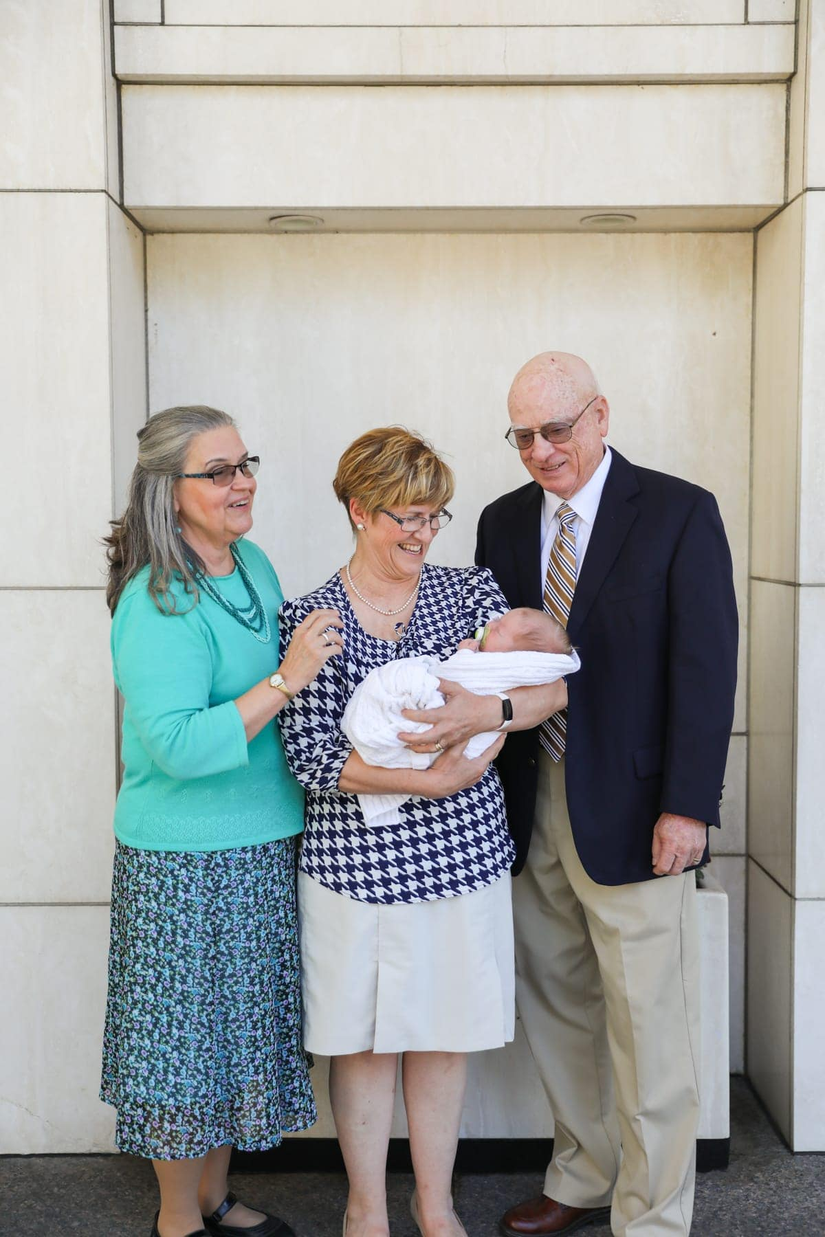 Grandparents holding Porter in front of a building