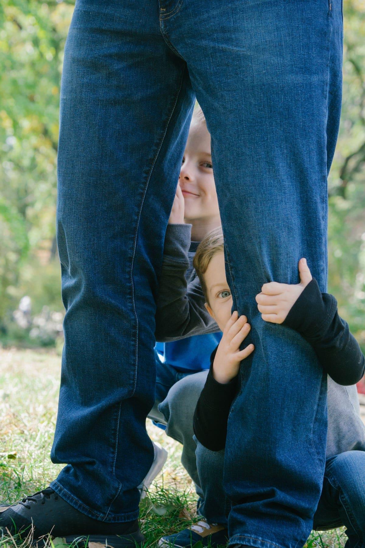 Eddie and Blake hiding behind legs