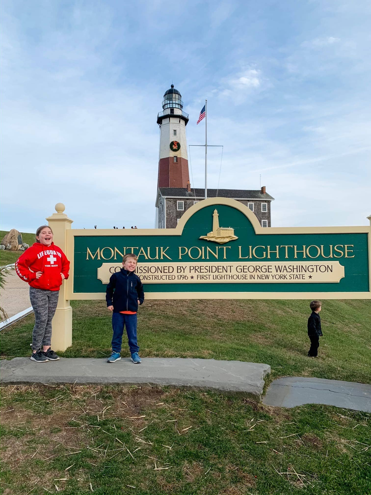 Kids standing in front of a lighthouse and sign