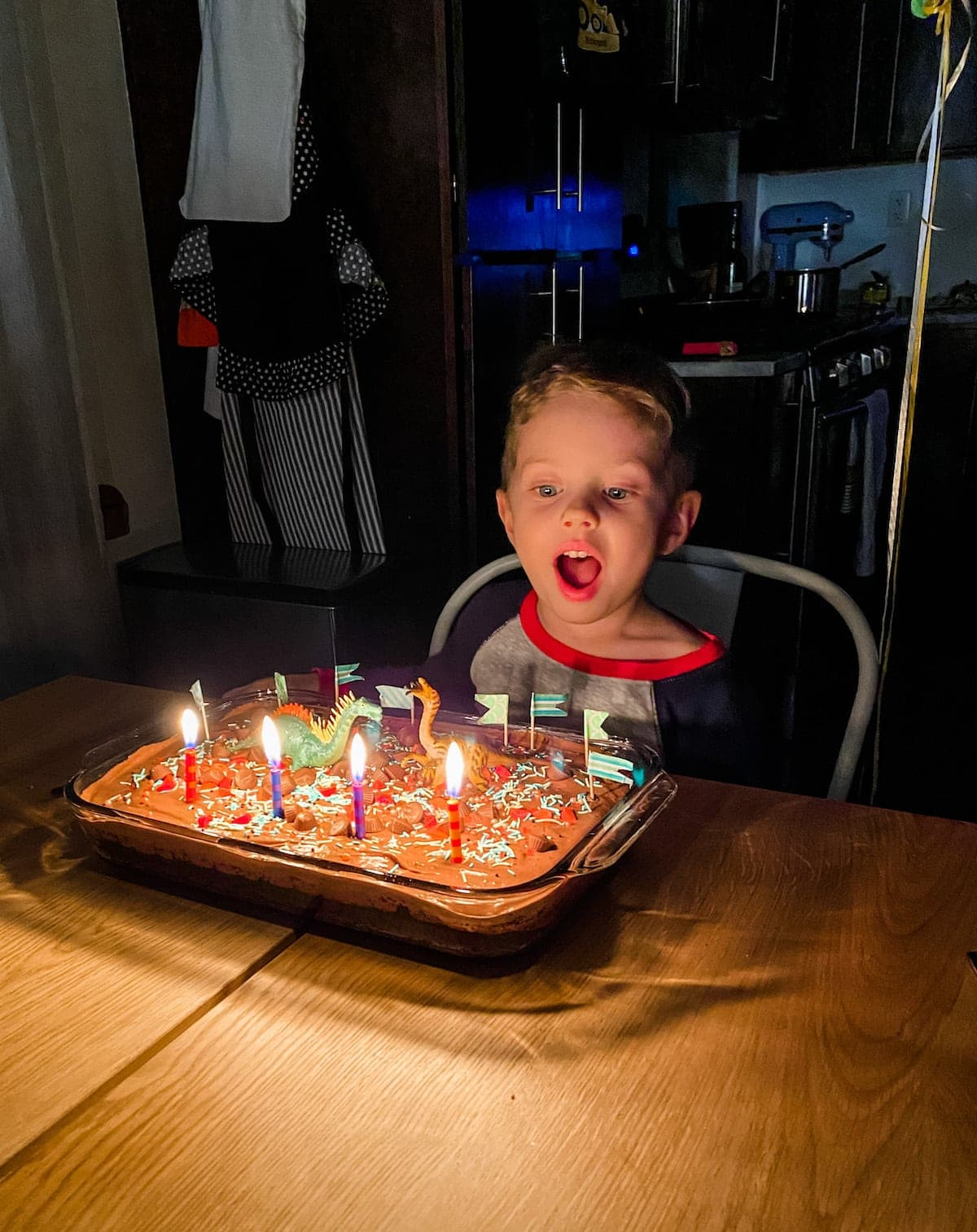 Eddie sitting at a table with a birthday cake with lit candles