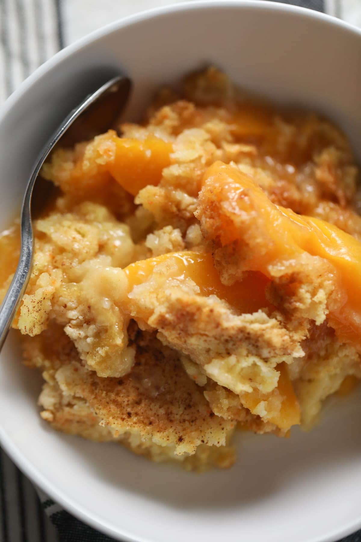 Peach Cobbler in white bowl with spoon
