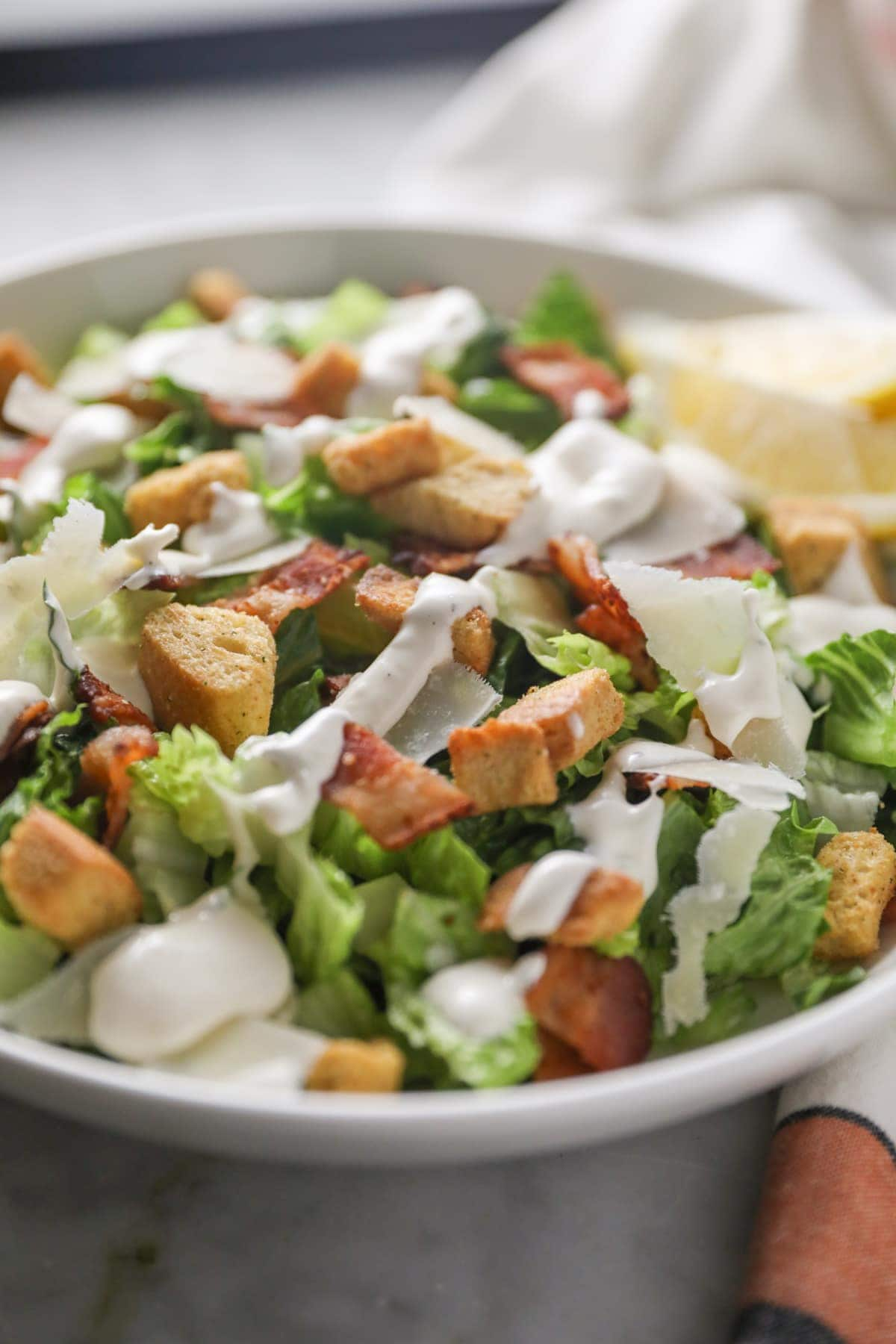 side view of caesar salad in a white bowl with dressing drizzled on top