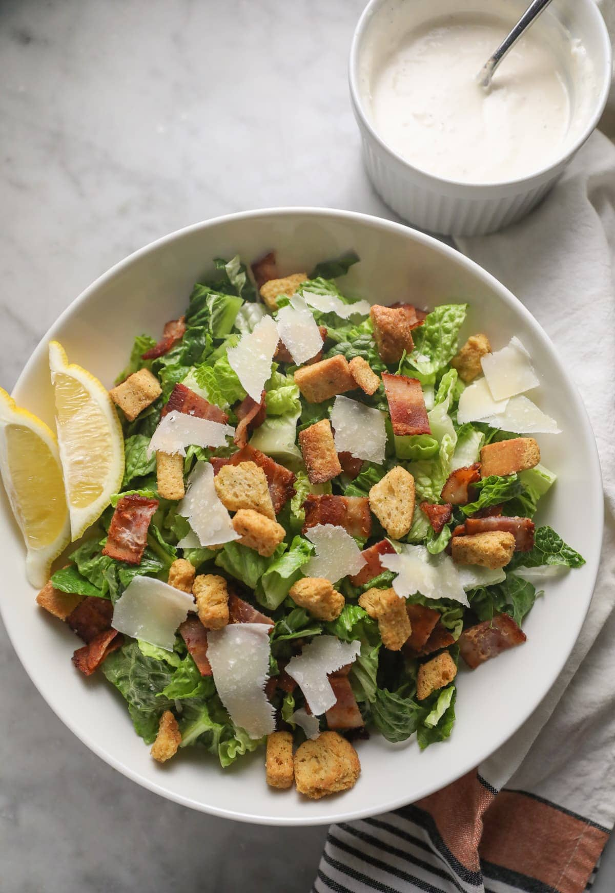 caesar salad in a white bowl with two lemon wedges on the side and caesar dressing in a small bowl on the side