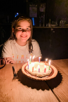 Brooke sitting at a table with a birthday cake with lit candles
