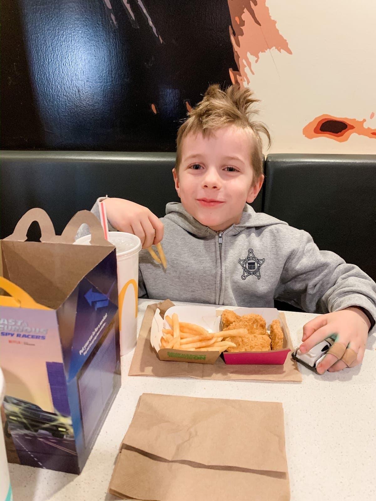 Blake sitting at a table eating McDonalds