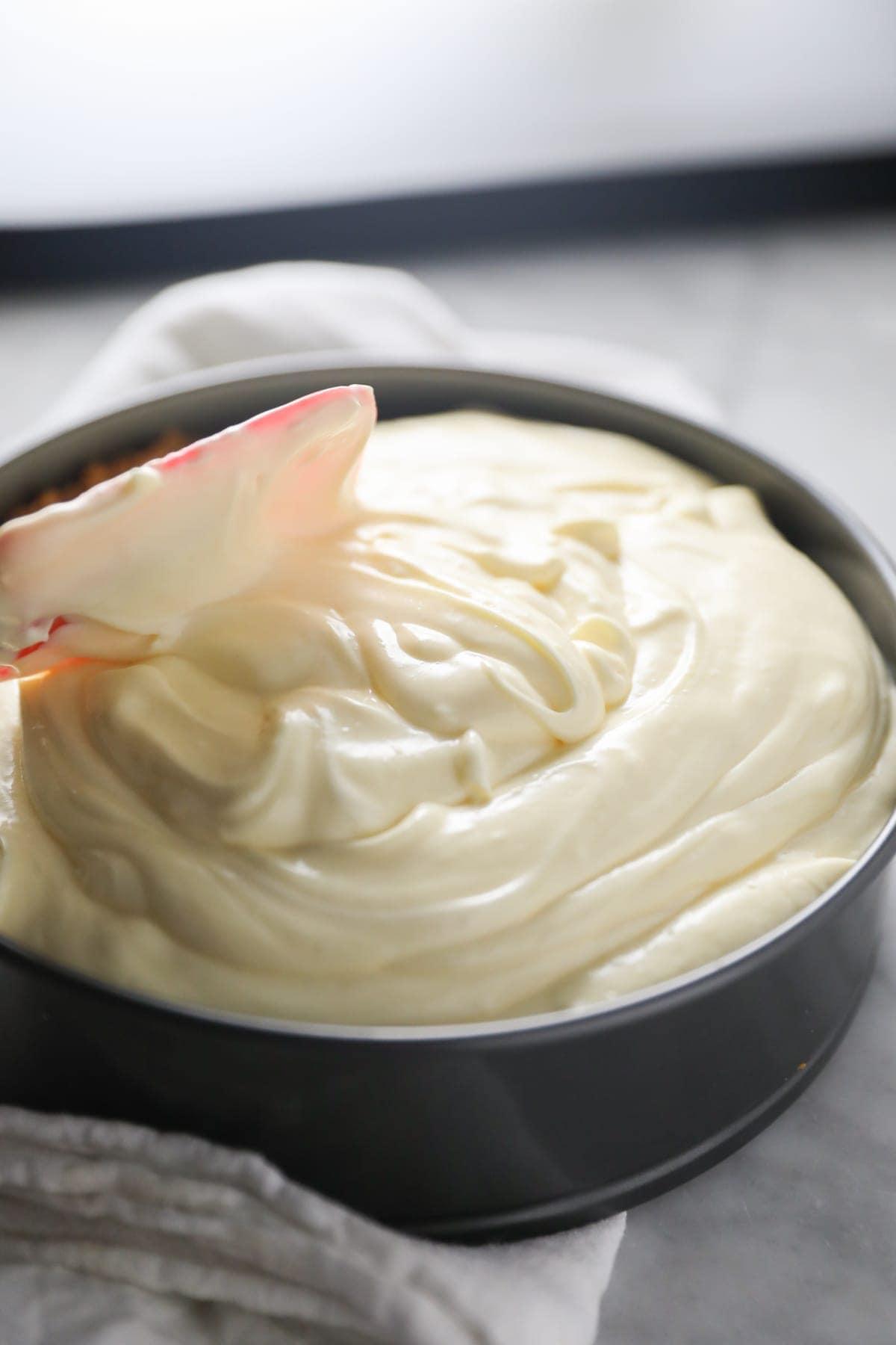 smoothing cheesecake batter into pan