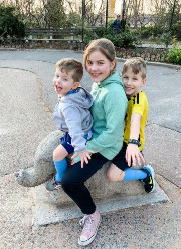 Eddie, Brooke and Blake sitting on a statue