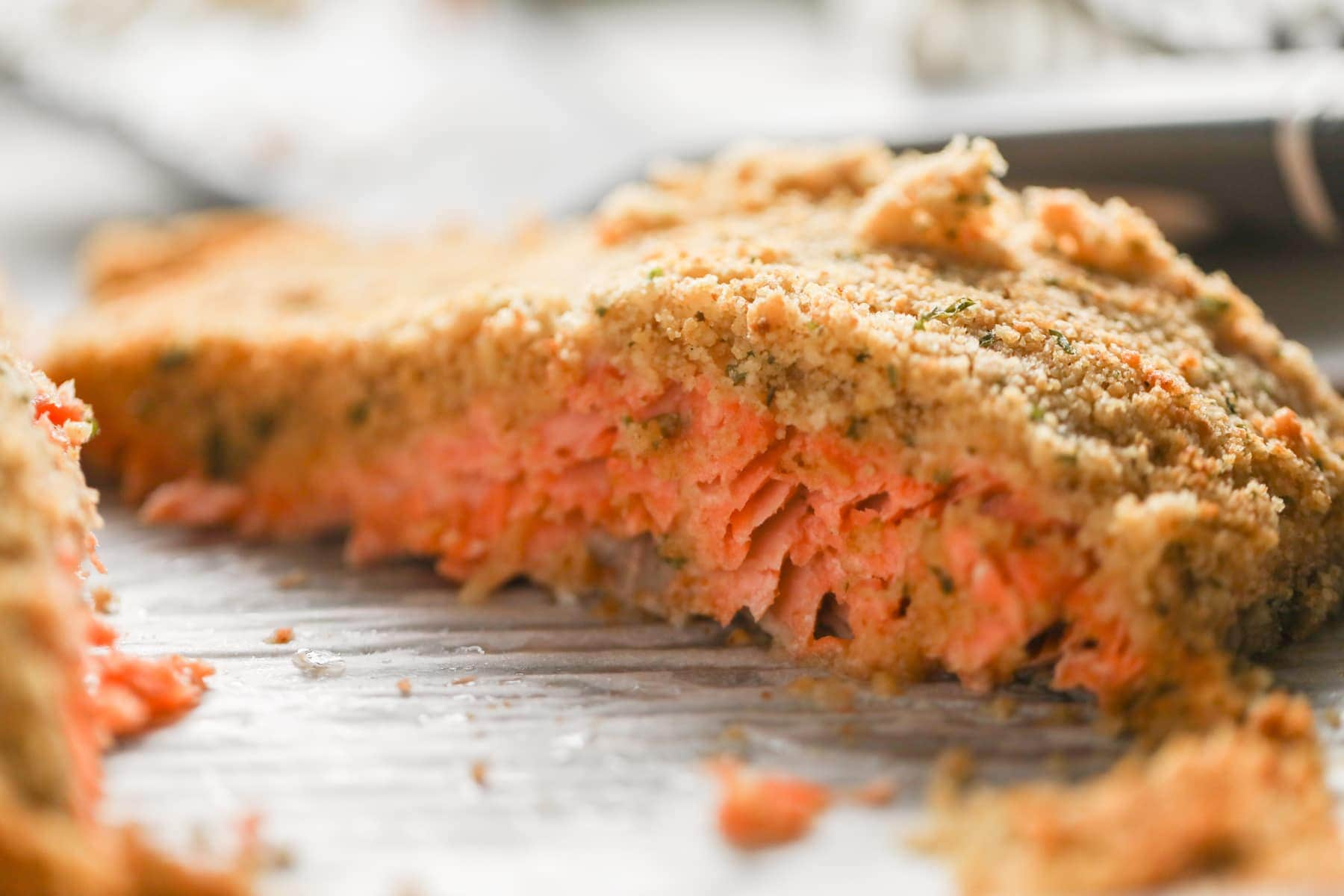 baked salmon topped with garlic butter breadcrumbs on tray