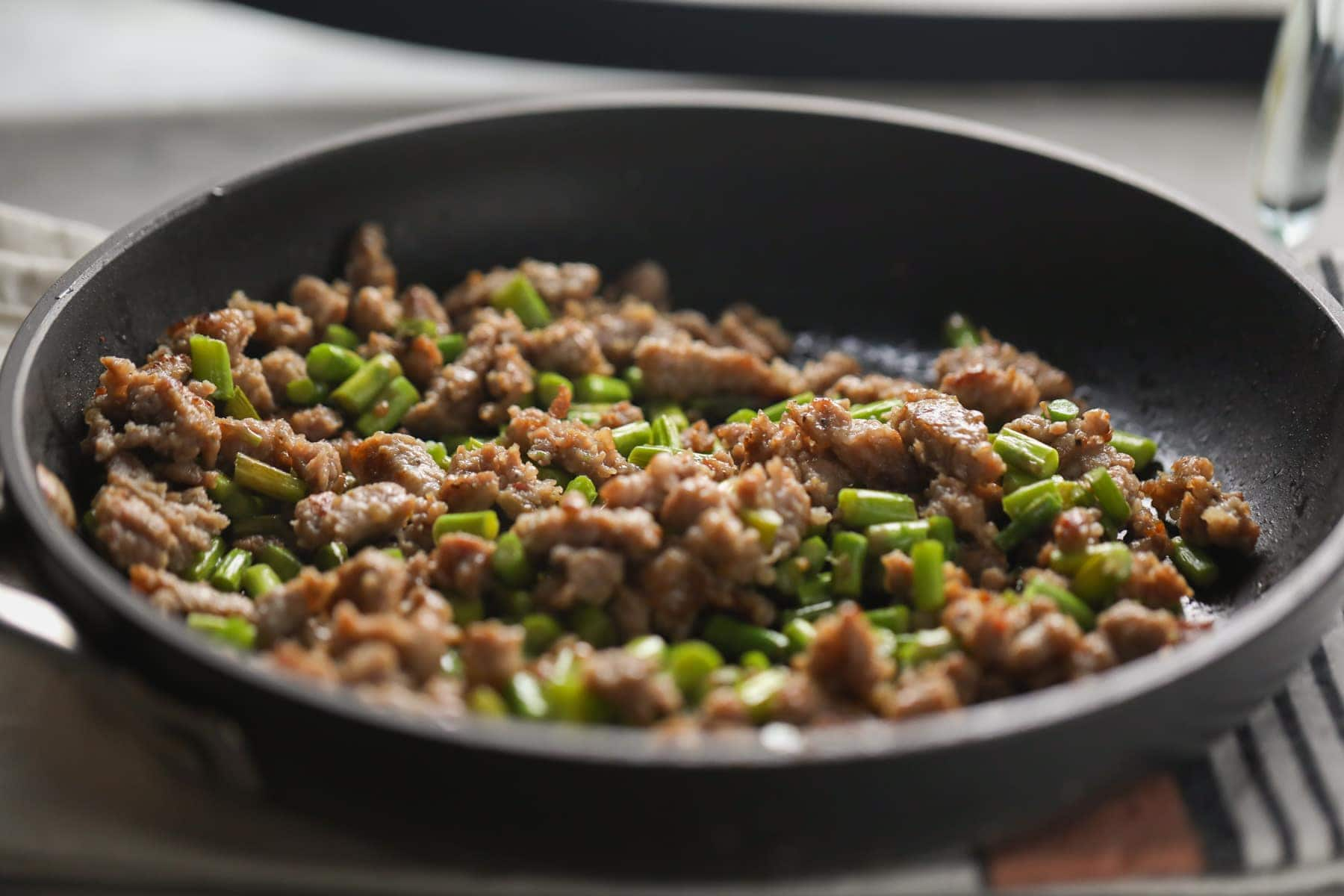 breakfast sausage and asparagus in a pan
