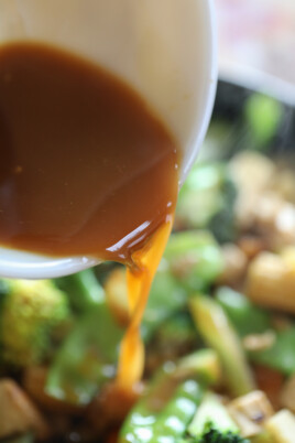 pouring stir fry sauce into pan