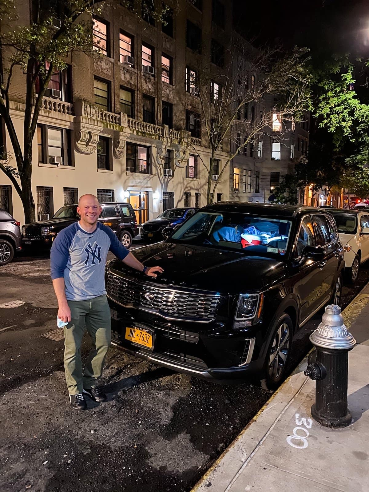 man standing in front of car on NYC street