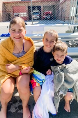 three wet kids wrapped in towels at pool