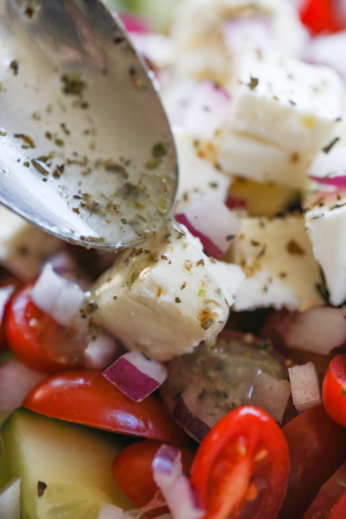 spooning dressing on greek salad